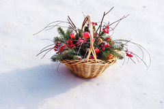 Composition of fir branches, rowan and apples. Composition of fir branches, rowan and apples in wicker basket on a background of snow Stock Image