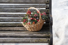 Composition of fir branches, rowan and apples. Composition of fir branches, rowan and apples in wicker basket on a background of snow and the old bench Royalty Free Stock Photos