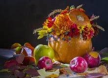 Composition florale dans un potiron La vie toujours avec un potiron, des fleurs et des pommes Fond foncé Images libres de droits