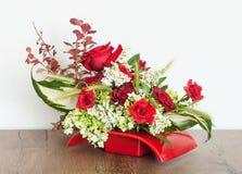 Composition florale de fantaisie dans un récipient rouge Photos stock
