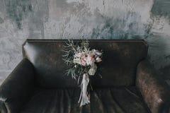 Composition florale rustique avec les roses légères et d'autres fleurs sur un sofa brun de luxe Image libre de droits