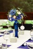 Composition florale sur la table de mariage Compositions florales avec les roses fraîches et les fleurs bleues Photographie stock libre de droits