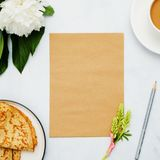 Composition with flower, pancakes, coffee and craft paper on white background. Mock up for your design. Flat lay. Top view Stock Images