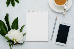 Composition with flowers, coffee, smartphone and notebook on white background. Mock up for your design. Flat lay. Top view Royalty Free Stock Photo