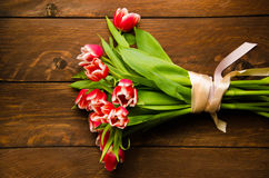 Composition of flowers collected by ribbon. A bouquet of tulips on a tree. Beautiful tulips on wooden boards. stock photos