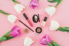 Composition with flowers and cosmetics on pink background. Top view. Flat lay. Home feminine desk. Composition with flowers and cosmetics on pink background stock photography