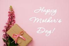 Composition with flowers and gift on pink background.Greeting card- happy mothers day. Flat lay. Composition with flowers and notebook on pink background Stock Images