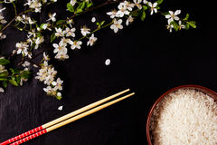Composition with flowers, rice and chopsticks on a black background Stock Image