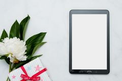 Composition with flowers and tablet pc on white background. Mock up for your design. Flat lay. Top view Royalty Free Stock Images