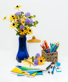 Composition with flowers in a vase and school supplies. Stock Photo