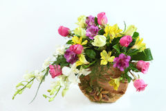 Composition with flowers. Composition with yellow, pink, purple and white flowers bouquet with white background and  handmade, natural material vase Stock Images