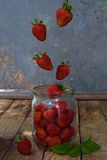 Composition of flying strawberry in jar. Cooking preparation compote or jam. Homemade conservation with organic fresh Royalty Free Stock Image