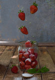 Composition of flying strawberry in jar. Cooking preparation compote or jam. Homemade conservation with organic fresh berry for th Royalty Free Stock Images