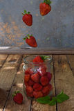 Composition of flying strawberry in jar. Cooking preparation compote or jam. Homemade conservation with organic fresh berry for th Royalty Free Stock Photos