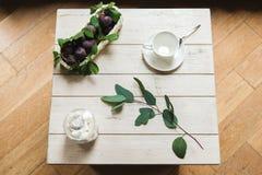Composition fraîche des prunes et de la tasse en céramique image stock
