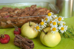 A composition with fresh apples, homemade apple pie, cinnamon sticks and a bouquet of chammomiles Royalty Free Stock Images