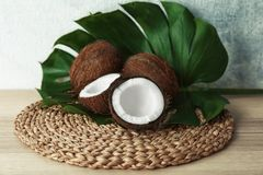 Composition with fresh coconuts and leaf. On wicker mat Stock Image