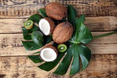 Composition with fresh coconuts and tropical fruits. On green leaf Stock Images