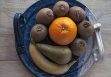 Ripe fresh fruits arranged on a decorative ceramic platter. Stock Image