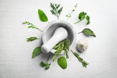Composition with fresh herbs and mortar. On wooden background stock photos