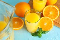 Composition with fresh orange juice in glassware, mint, and cutting board with oranges on color background, closeup. Fresh natural. Drink stock photography