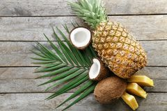 Composition of fresh pineapple and coconuts. On wooden background Stock Images