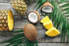 Composition of fresh pineapple and coconuts. On wooden background Royalty Free Stock Photography