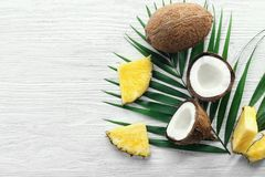 Composition of fresh pineapple slices and coconuts. On light wooden background Royalty Free Stock Photo