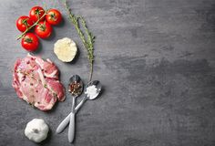 Composition with fresh raw steak, vegetables and spice. On table Royalty Free Stock Images