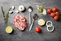 Composition with fresh raw steak, vegetables and spice. On table Royalty Free Stock Image