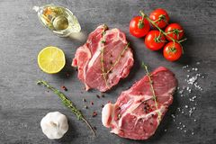 Composition with fresh raw steaks, thyme and vegetables. On table Stock Photo