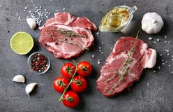 Composition with fresh raw steaks, vegetables and spice. On table Royalty Free Stock Photos