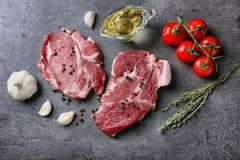 Composition with fresh raw steaks, vegetables and spice. On table Stock Photos
