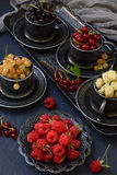 Composition of fresh ripe berries: red, black and white currant, mulberry on a dark gray concrete background. Dark photo. Photogra Stock Image