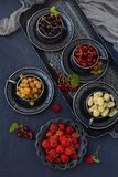 Composition of fresh ripe berries: red, black and white currants on a dark gray concrete background. Dark photo. Photographing in royalty free stock photos