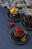 Composition of fresh ripe berries: red, black and white currants on a dark gray concrete background. Dark photo. Photographing in royalty free stock photo