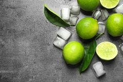 Composition with fresh ripe limes and ice cubes. On gray background, top view Stock Images