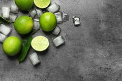 Composition with fresh ripe limes and ice cubes. On gray background, top view Stock Photography