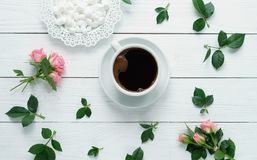 Composition of fresh roses , cup of coffee, varshmallows on a white wooden background. top wiew Stock Images