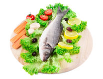 Composition of fresh seabass with carrot. Composition of fresh seabass and vegetables. Isolated on a white background Royalty Free Stock Photo