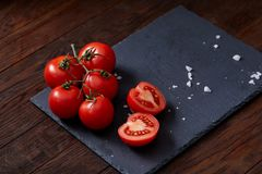 Composition with fresh tomatoes on wooden background, close-up, selective focus. Composition with fresh tomatoes on black flat piece of board over wooden royalty free stock photography