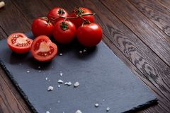 Composition with fresh tomatoes on wooden background, close-up, selective focus. Composition with fresh tomatoes on black flat piece of board over wooden stock photography