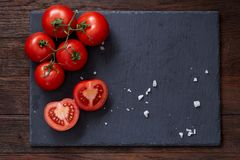 Composition with fresh tomatoes on wooden background, close-up, selective focus. Composition with fresh tomatoes on black flat piece of board over wooden royalty free stock photo