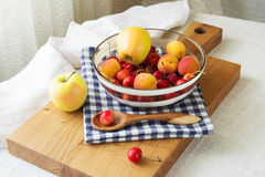 Composition of fruits and berries. Reason for the longevity is apples, cherries, apricots. Fruits and berries in a bowl on a checkered napkin on the table Royalty Free Stock Photography