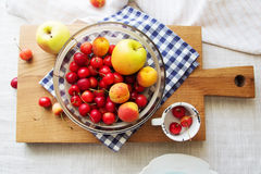 Composition of fruits and berries. Reason for the longevity is apples, cherries, apricots. Fruits and berries in a bowl on a checkered napkin on the table Royalty Free Stock Photo