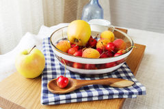 Composition of fruits and berries. Reason for the longevity is apples, cherries, apricots. Fruits and berries in a bowl on a checkered napkin on the table Stock Image