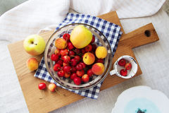 Composition of fruits and berries. Reason for the longevity is apples, cherries, apricots. Fruits and berries in a bowl on a checkered napkin on the table Royalty Free Stock Photos
