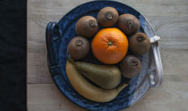 Composition of fruits on a decorative blue platter on a wooden board with a black cloth in the background royalty free stock image