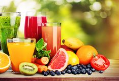 Composition of fruits and glasses of juice on. Juice composition glasses fruits background natural blurred Royalty Free Stock Images