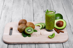 Composition of fruits and vegetables. Avocados and kiwis next to a glass of spicy green cocktail on a wooden background. A colorful composition of organic royalty free stock photo